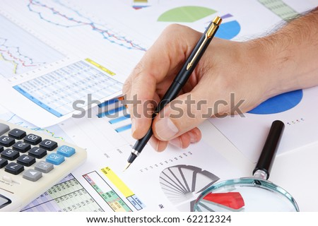 pen in hand and working paper chart - stock photo