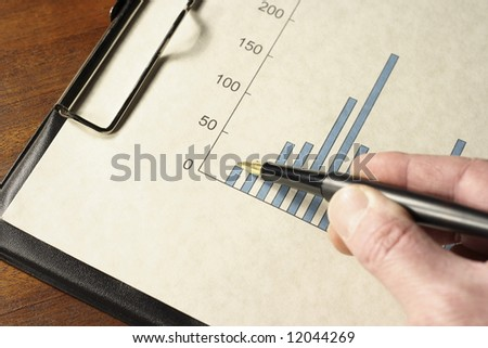 Pen in hand pointing at a bar graph on a clipboard. - stock photo