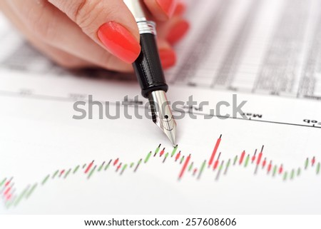 Pen in hand with candle stick chart - stock photo