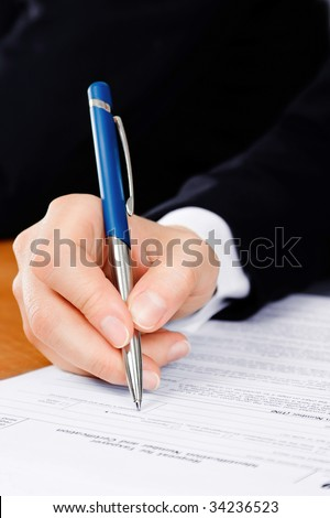 Pen in man's hand, filling the tax form - stock photo