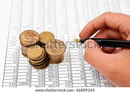 Pen in man's hand on financial document. Studio shot - stock photo