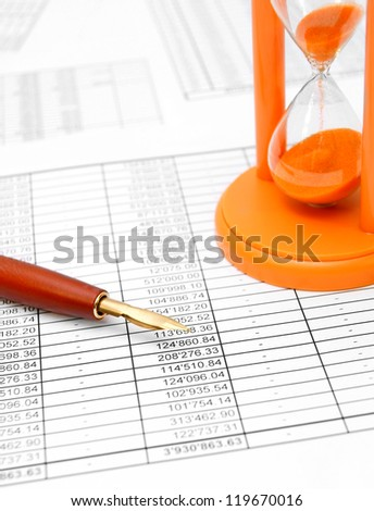 Pen, ink and a sand-glass on documents. - stock photo