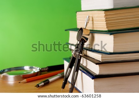 pen, ink pen, pile of books and magnifying glass on wood table - stock photo