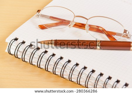 Pen, notebook and glasses on office desk. Selective focus on pen - stock photo