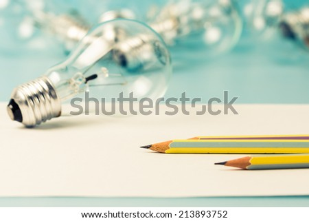 Pen on clear paper with light bulb as creative writing concept - stock photo