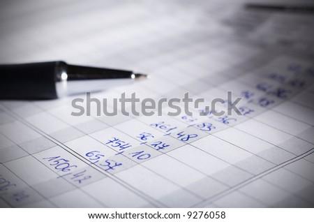 Pen on financial document. Macro. Shallow DOF. - stock photo