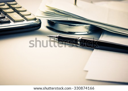 Pen on many receipts with part of paper nail and calculator for financial concept
