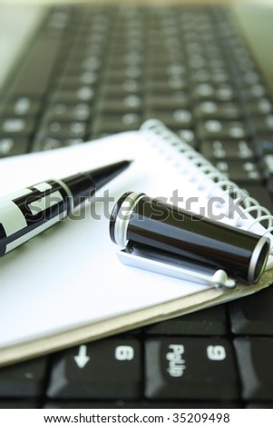 Pen on notebook and laptop computer. - stock photo