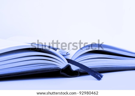 Pen on notebook organizer close-up in blue - stock photo