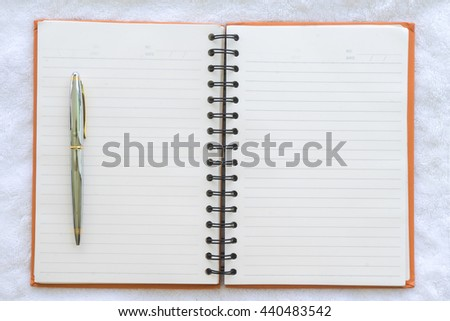 pen on notebook with fabric background, Top view