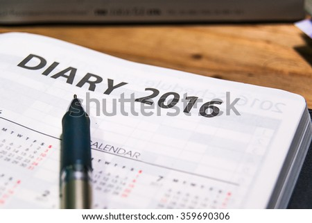 pen on open diary book 2016 calendar page with calendar page on wood table - stock photo