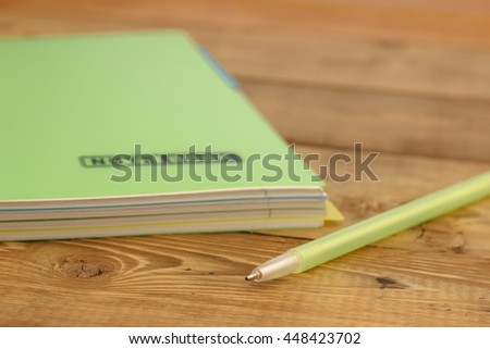 pen on the closed notebook lying on a wooden table