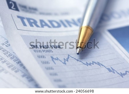 Pen over depressing newspaper stocks graph.  Soft-focus, with shallow depth of field.