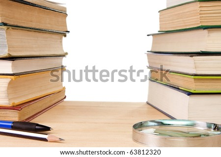 pen, pencil, pile of old books and magnifier isolated on white - stock photo