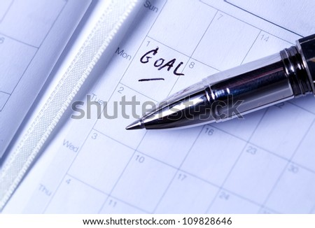 "pen put on diary that write ""GOAL"" letter"