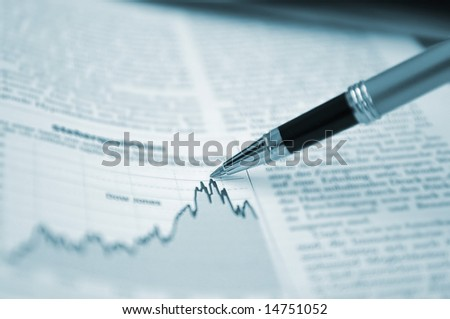 Pen showing diagram on financial report/magazine