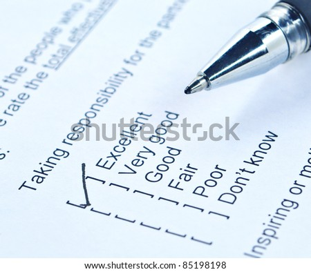 Pen tick on responsibility quality survey form - stock photo