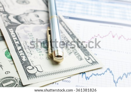 Pen with dollar bank note on graph analysis forex trading - stock photo