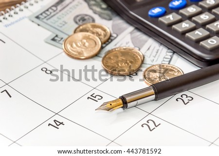 Pen with dollar coins and calculator on calendar - stock photo