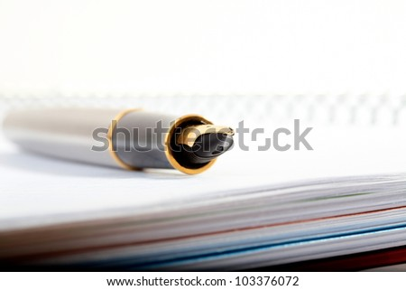 pen with feather lays on a writing-book with spiral - stock photo