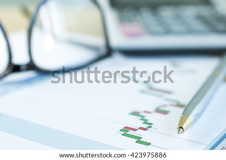 Pen with stock graph paper and blur eyeglasess and calculator - stock photo