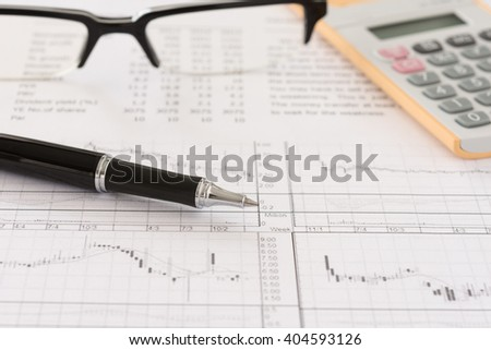 Pen with stock trend analysis report, calculator, glasses on desk of investors. Concept of business, finance, investment, financial service. - stock photo