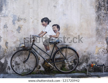 PENANG, MALAYSIA-DEC 8: General view of a mural 'Little children on a bicycle' painted by Ernest Zacharevic in Penang on Dec.8, 2012. The mural is one of the 9 murals painted by him in early 2012. - stock photo