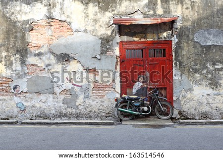 PENANG, MALAYSIA - DEC 13: Street art titled Boy on a Bike by Ernest Zacharevic in  Penang on Dec 13, 2012. It was painted under the Mirrors George Town project for the 2012 George Town Festival. - stock photo