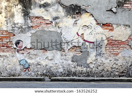 PENANG, MALAYSIA-DEC 13: Street art titled Little Boy with Pet Dinosaur by Ernest Zacharevic in Penang on Dec 13, 2012. It was a Mirrors George Town project for the 2012 George Town Festival. - stock photo