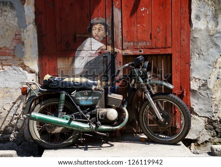 PENANG, MALAYSIA-DEC.9: Street Mural entitled 'Boy on a bike' painted  by Ernest Zacharevic in Penang on Dec.9, 2012. It was painted in conjunction with the 2012 George Town Festival. - stock photo
