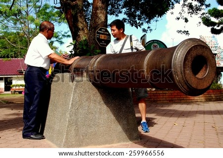 Penang, Malaysia - January 10, 2008:  Visitors on Penang Hill examine an 18th century English cannon at the summit of the mountain - stock photo