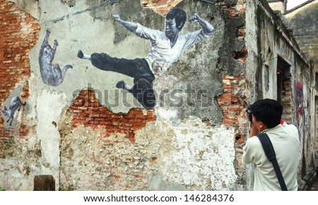 PENANG, MALAYSIA-JULY 6: Tourist takes a photograph of a street mural painting 'The Real Bruce Lee Would Never Do This' painted by 101 Lost Kittens in Penang on July 6, 2013. - stock photo
