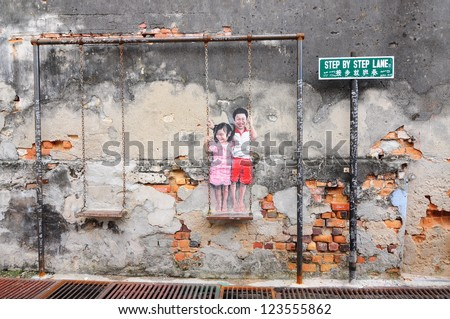 PENANG, MALAYSIA-NOV 24: General view of a mural 'Children on the Swing' painted by Louis Gan in Penang on November 24, 2012. This art work can be found at Chulia Street . - stock photo