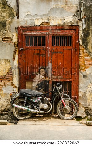 PENANG, MALAYSIA - OCTOBER 23, 2014 : General view of a mural 'Boy on a Bike' painted by Ernest Zacharevic in Penang. The mural is one of the 9 murals paintings in early 2012.  - stock photo