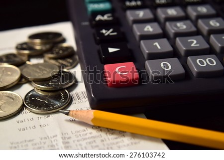 Pencil and Calculator beside the Bill and Coins - stock photo