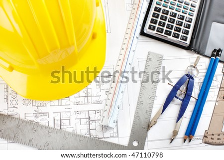 pencil and calculator over a construction drawing of a house - stock photo