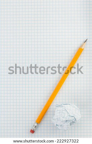 pencil and crumpled paper ball on checked background - stock photo