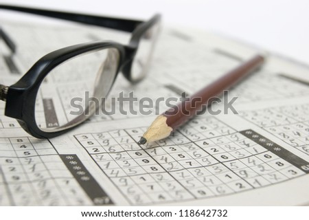 Pencil and glasses on a sudoku game - stock photo