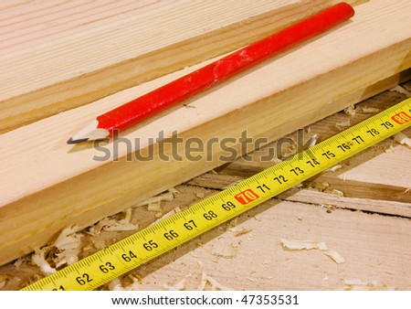 Pencil and measure tape on wooden plane - stock photo