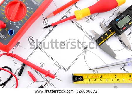Pencil and measuring tape and Digital multimeter and vernier caliper and screwdrivers on plans - stock photo