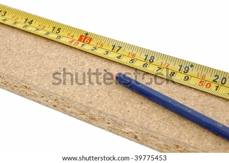 Pencil and measuring tape on a plank of wooden chip board