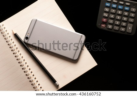 Pencil and mobile phone on Notebook with calculator use in business office black background - stock photo