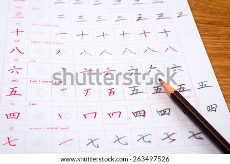 Pencil and notebook for learning Chinese hieroglyphs.