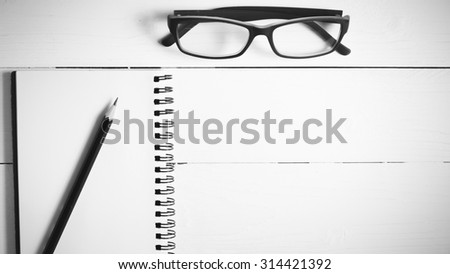 pencil and notepad with eyeglasses over white table view from above black and white color style