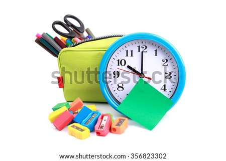 pencil case full of school supplies and blue watch on white background with green memo - stock photo