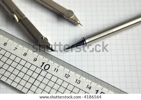 Pencil compass and ruler on white graph paper