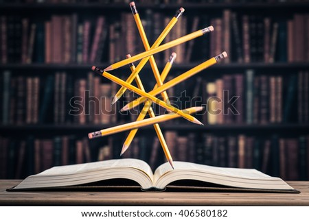 Pencil floating on the heavy books - stock photo