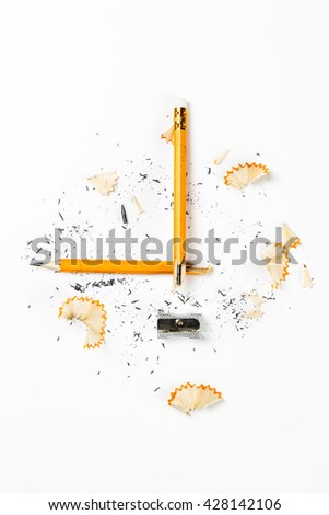 Pencil, metal sharpener and pencil shavings on white background. Vertical image.