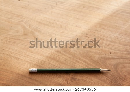 Pencil on a rustic wooden desk, in natural window lighting. Shallow depth of field. Focus is on the forehand pencil. - stock photo
