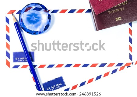 Pencil on air mail envelopes with blue crystal and passports on white background - stock photo